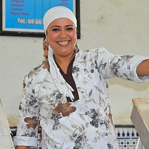 A Moroccan female fish vendor holds up a large fish for sale while smiling broadly.