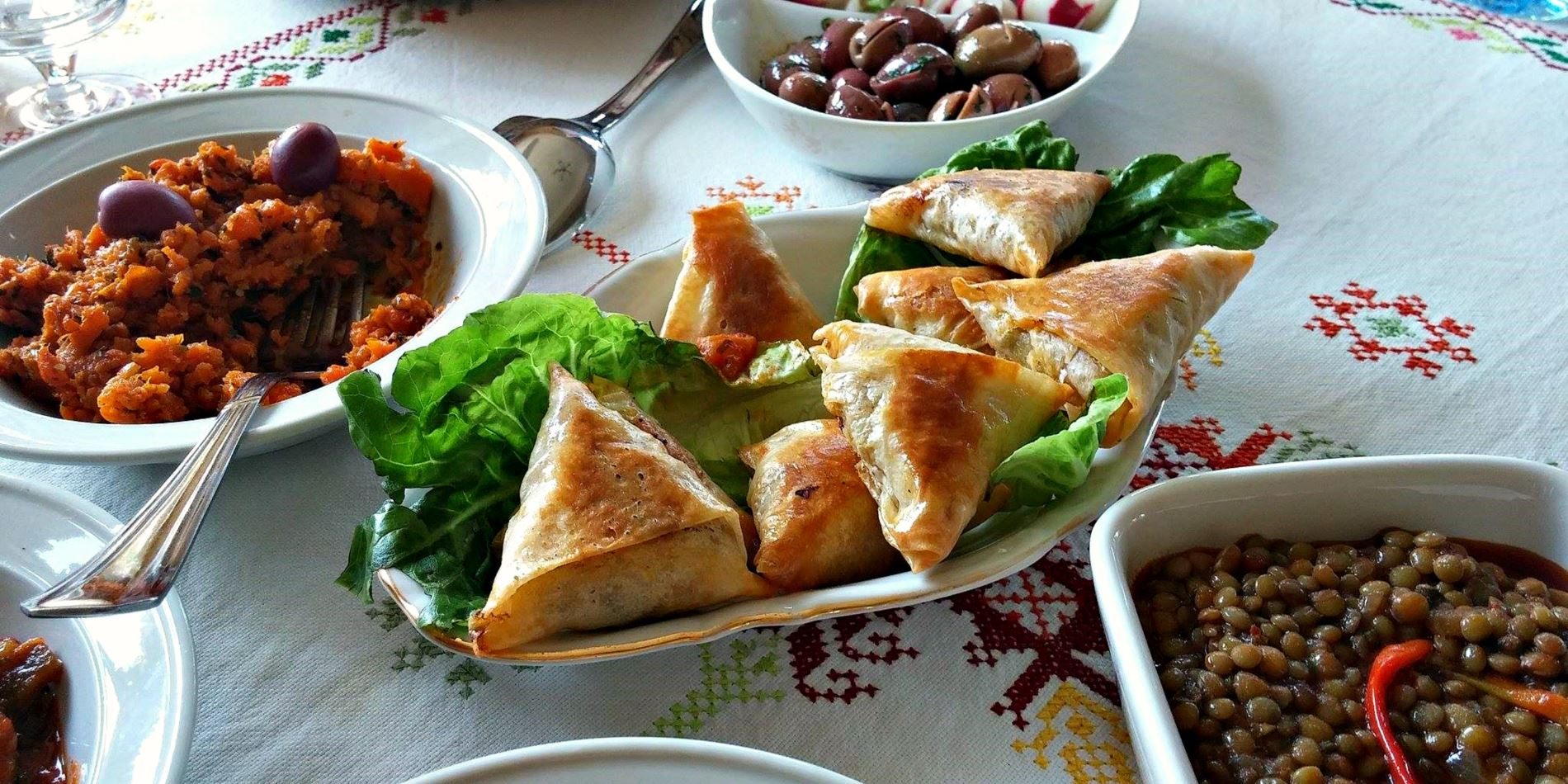 Moroccan savory pastries, lentils, carrot salad and olives are served as starters at a Moroccan meal for tourists in a Casablanca home.
