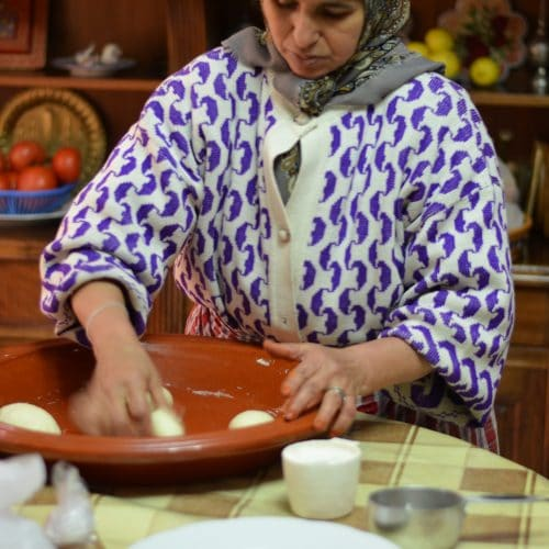 Moroccan woman kneads and shapes dough in a wide shallow ceramic dish.
