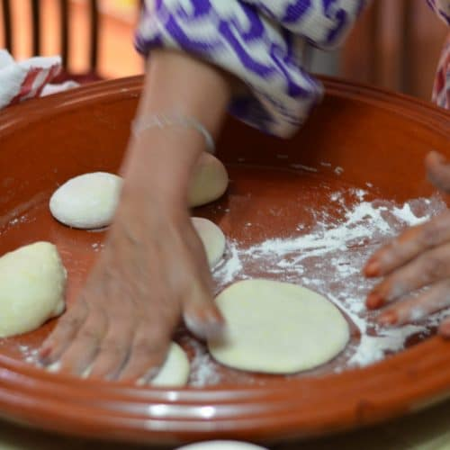 Close up photo of woman's hands patting and shaping rounds of dough in a very wide, shallow ceramic bowl.