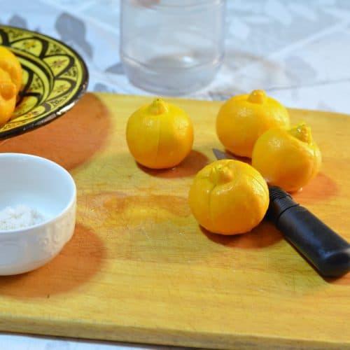 Lemons sit on a wooden cutting board alongside a knife and bowl of coarse salt.