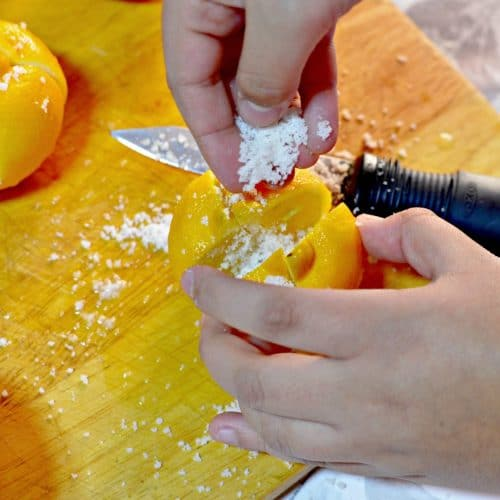 Close-up of hands adding coarse salt to a partially cut lemon as the first step of making preserved lemons.