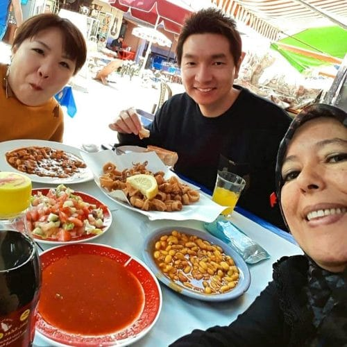 Two tourists pose for a selfie with a guide while enjoying a seafood lunch at Marche Central in Casablanca.