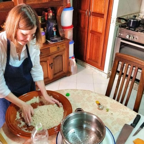 A woman tosses gluten free couscous grains by hand at a Moroccan cooking class in Casablanca.
