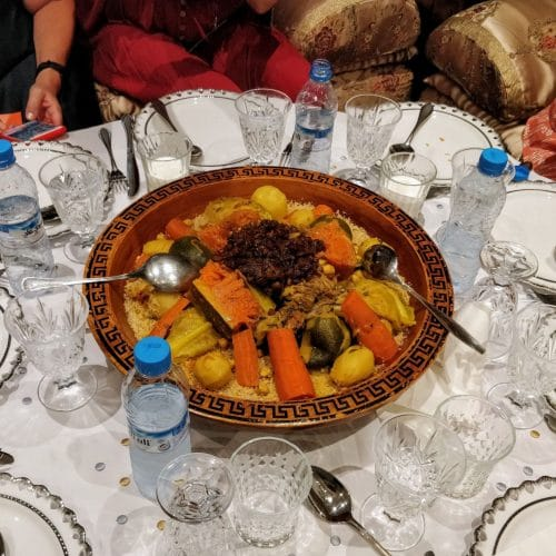A large platter of couscous sits in the middle of a table at a Moroccan cooking class in Casablanca.