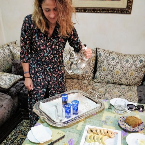 A woman pours tea from a Moroccan tea pot at an in home Moroccan cooking class in Casablanca.