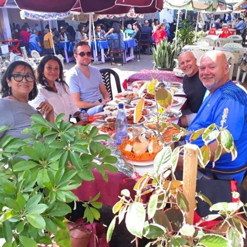 A group of five people sits at a table full of fish and seafood at Central Market in Casablanca.
