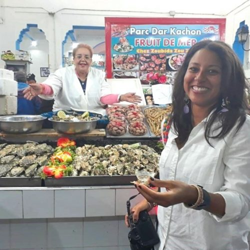 A smiling woman holds a raw oyster in front of a seafood stall in Casablanca's Central Market. A smiling female Moroccan fish vendor smiles and gestures in the background.