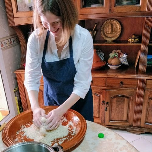A woman learns to toss couscous by hand at a gluten free Moroccan cooking class in Casablanca.