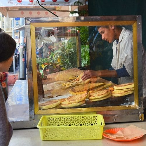 A Moroccan vendor serves tourists some of the stove top breads he sells.