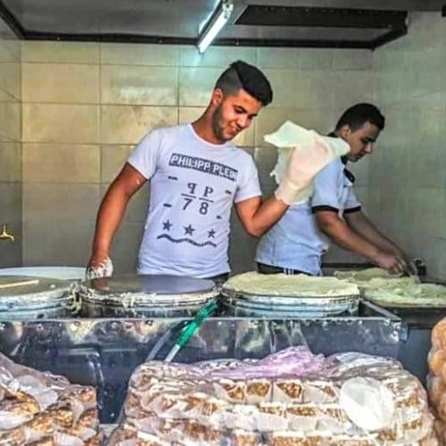 Moroccan street food seen on a food tour in Casablanca. Cookies on trays and in the background are two men making Moroccan warqa pastry.