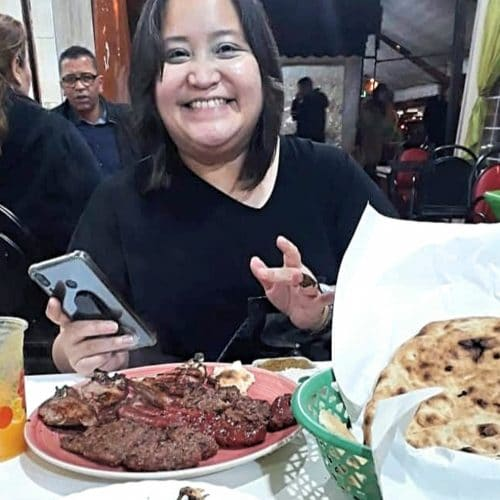 A woman with medium length brown hair smiles as she holds a cell phone and sits in front of grilled foods during a Moroccan food tour in Casablanca.