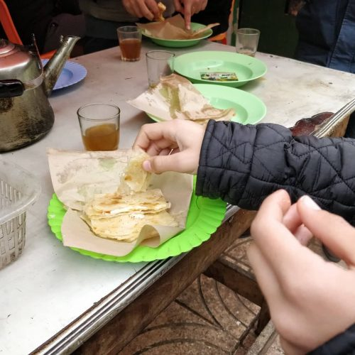 Closeup of msemen and Moroccan tea on a table at a stop on a Moroccan street food tour in Casablanca. The hands and arms of some guests can be seen.