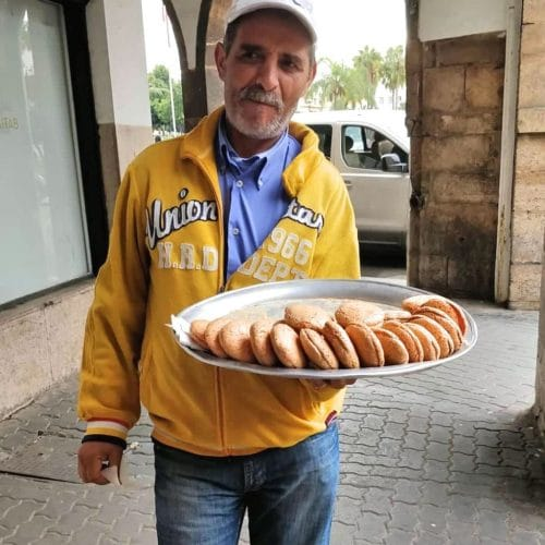 An older Moroccan man in yellow jacket holdsout a tray of Moroccan macaroons. He was seen on a Moroccan food tour in Casablanca.