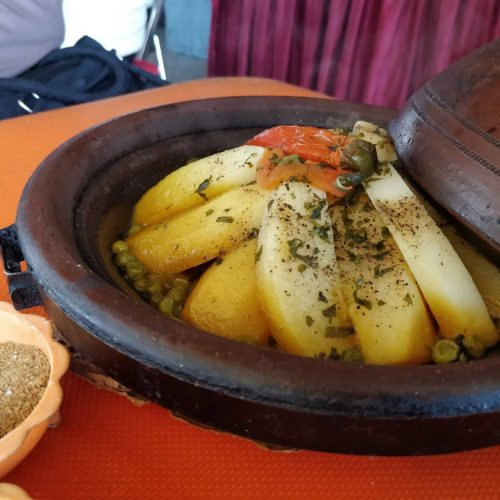Close up photo of a Moroccan tagine with wedges of potatoes.
