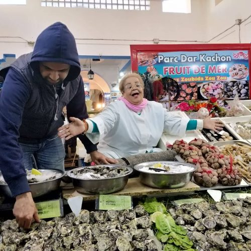A laughing woman fish vendor holds out her arms while a man in a hooded sweatshirt arranges shellfish at a Casablanca seafood market.