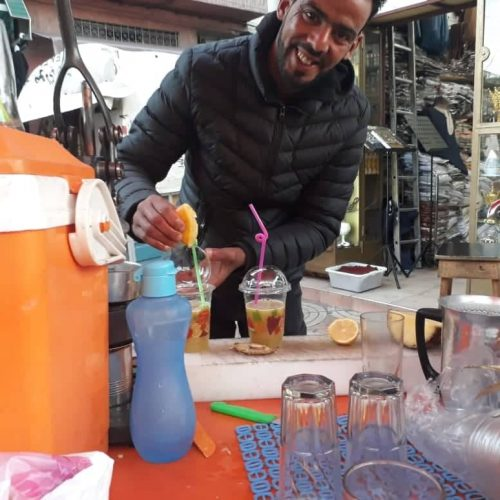 A smiling man prepares sugar cane juice in Casablanca.