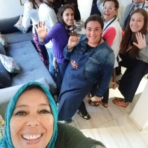 A group of university students at a cooking class in Casablanca pose for a selfie with tour guide. The kids are smiling and wearing Taste of Casablanca aprons.