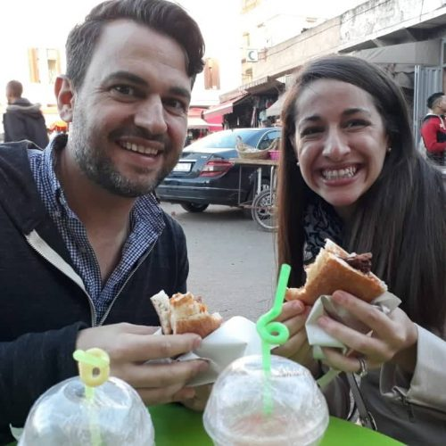 A smiling man and woman hold sandwiches at a table on a Casablanca street food tour. The tops of juice cups with straws is in the foreground.