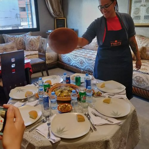A young African American woman wearing a Taste of Casablanca apron and glasses lifts the top off of a tagine. The tagine is being served at the meal following a Moroccan cooking class.