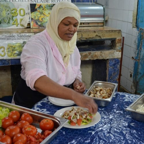 A woman with hijab sits at a table and prepares a seafood salad in Casablanca's Central Market.