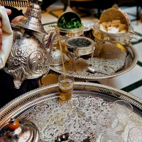 Closeup image of tea pouring from the long spout of an engraved metal Moroccan tea pot. The tea glass sits on an engraved metal tray with another tray and engraved tea, sugar and mint dishes in the background.