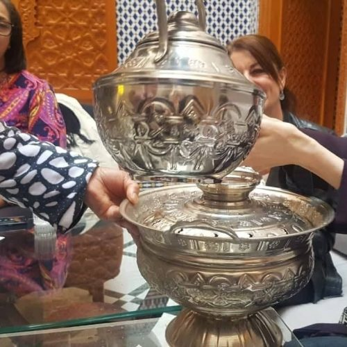 A woman's hands are extended as water is poured from an engraved metal Moroccan tass. Two seated in the background can be partially seen.