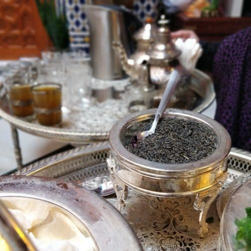 A silver dish holding green tea and a spoon sits on an engraved metal tray. In the blurred background is another tray with Moroccan tea glasses and a tea pot.