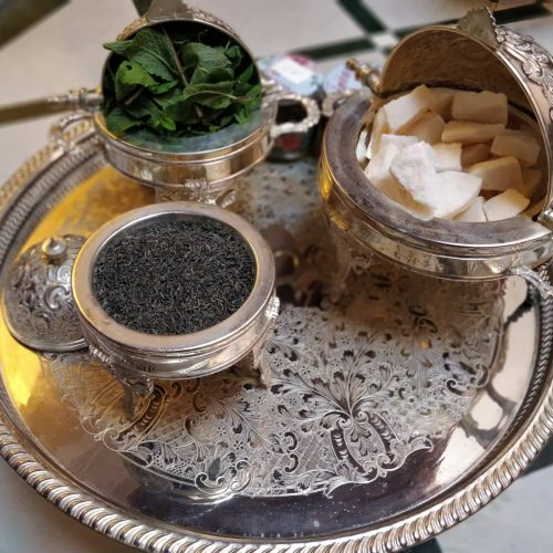 Three engraved silver dishes sit on a round engraved metal tray. The dishes hold sugar cubes, fresh mint, and green tea.
