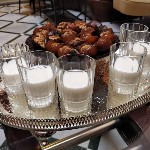 An engraved metal tray holds six glasses half full of milk and a plate of Moroccan stuffed dates.