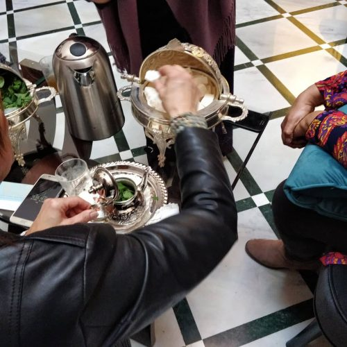 A woman whose face is not visible reaches for sugar cubes to place into the small tea pot in front of her as she learns to make Moroccan tea.