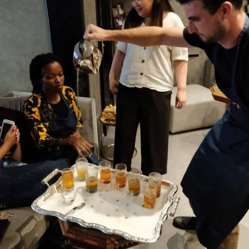 Young man pours Moroccan tea while others look on.